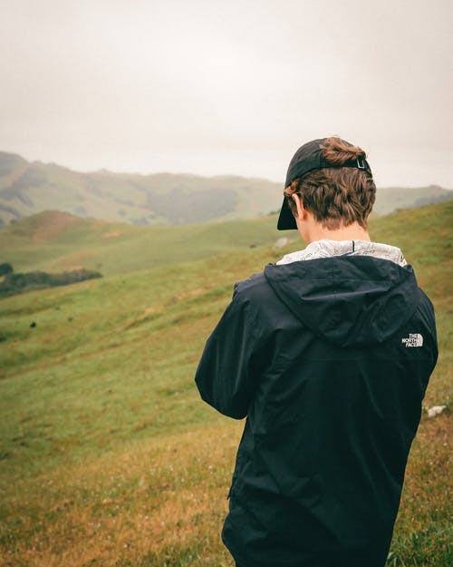 Man in Black Jacket Standing on Green Grass Field