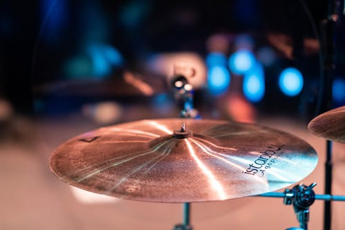 Cymbals with shiny surface and bell in center on stage with artificial lights on blurred background