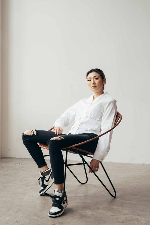 Full body of confident ethnic female wearing ripped jeans with blouse and sneakers sitting in armchair in studio