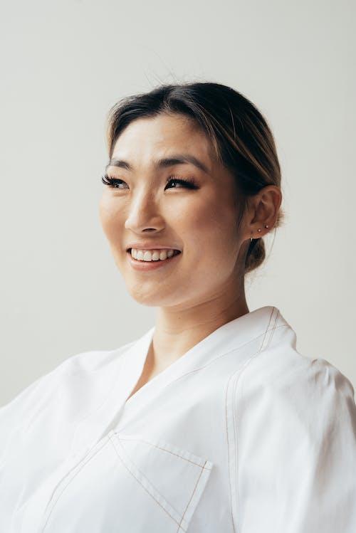 Positive Asian woman wearing white blouse in studio