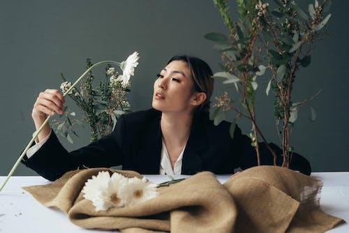 Elegant Asian woman with blooming flower in studio