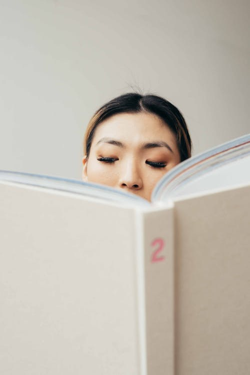 Serious Asian woman reading textbook with interest