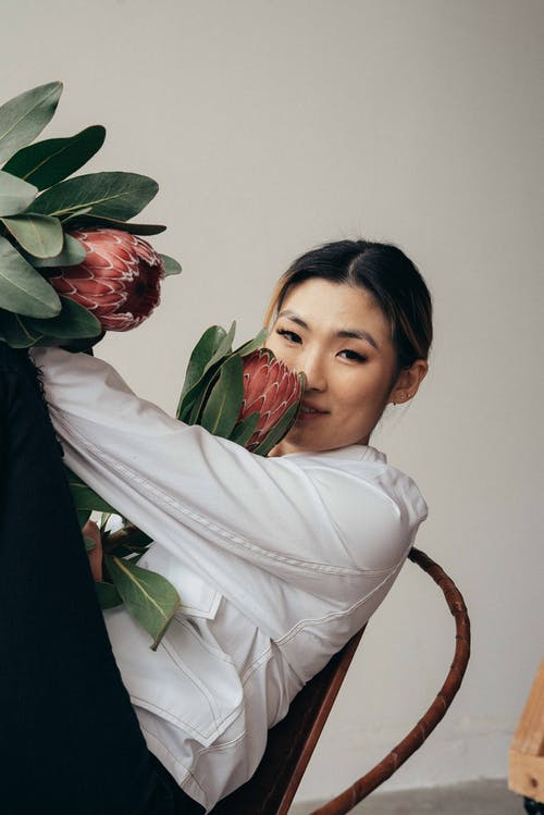 Happy Asian female in white shirt smelling protea flower with green leaves while sitting on chair and looking at camera on white background