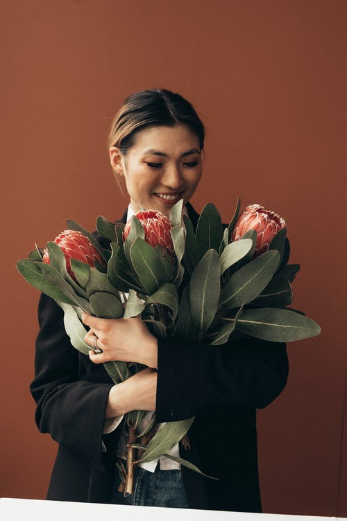 Cheerful Asian woman looking at flowers