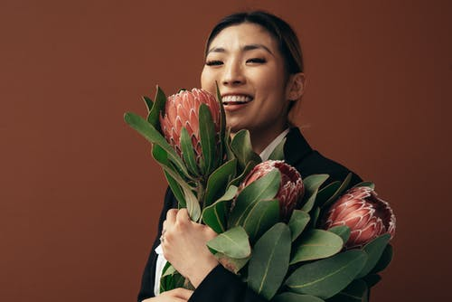 Smiling Asian female with bouquet of blooming pink protea flowers with green leaves standing on brown background in light studio