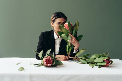 Gentle Asian woman smelling Protea flowers at table in studio