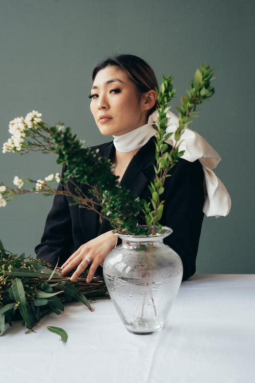 Gentle Asian woman with white scarf near vase with flowers