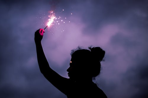 Woman Holding Lighted Sparkler in Grayscale Photography