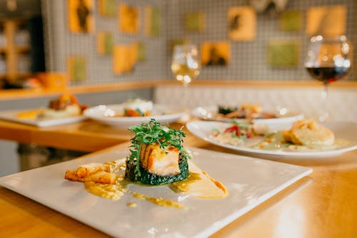 Various appetizing dishes served on white plates and glasses of wine on wooden table in modern light restaurant