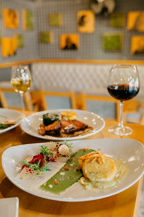 Appetizing delicious dishes on white round plates on wooden table wine glasses of wine in restaurant
