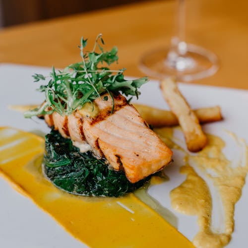 Closeup of delicious grilled salmon fillet and spinach served on white plate with french fries and sauce on table in restaurant