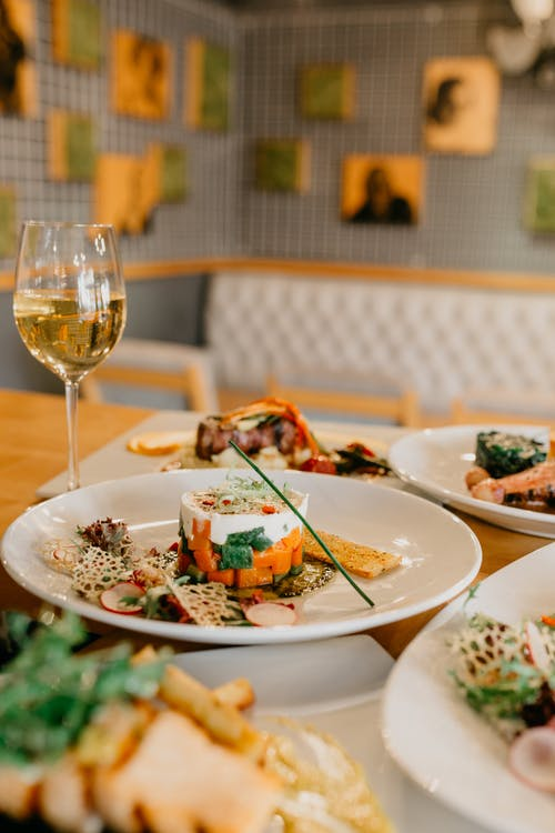 Served table with various delicious dishes and glass of white wine in modern restaurant on blurred background