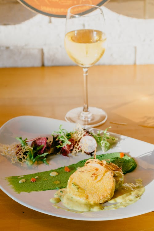 Delicious served dish and white wine in restaurant