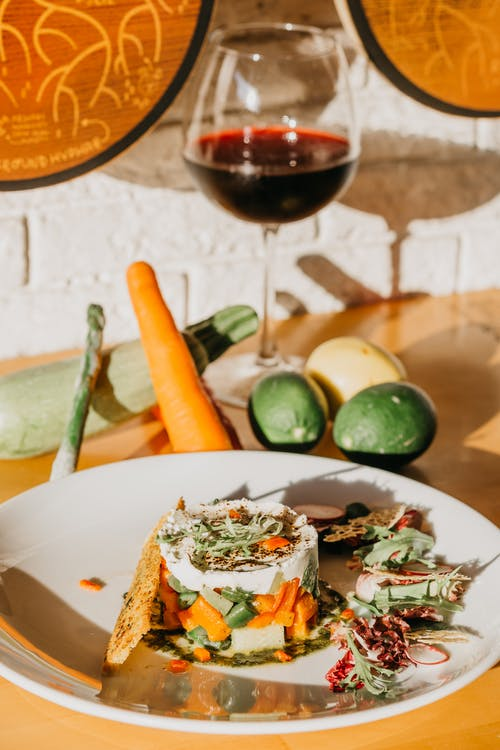 From above of tasty healthy vegetable tart with glass of red wine served on wooden table near raw fresh carrot zucchini and limes in kitchen