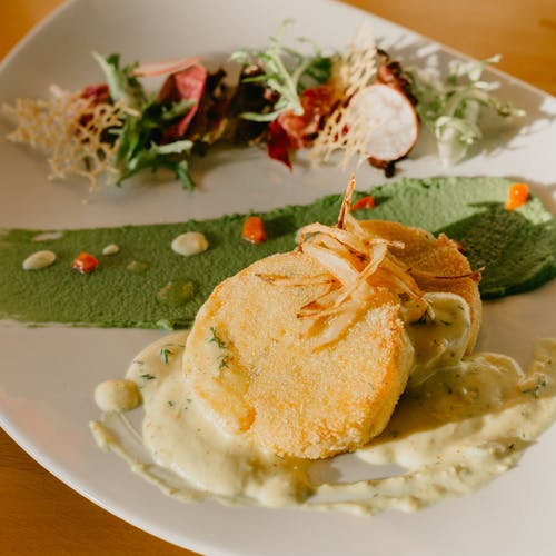 Delicious saucy potato cutlet with salad served on plate
