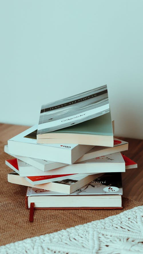 Stack of different interesting books placed on beige rug on wooden floor at home with white walls