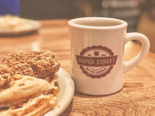 White and Brown Maple Street Ceramic Mug Beside Food