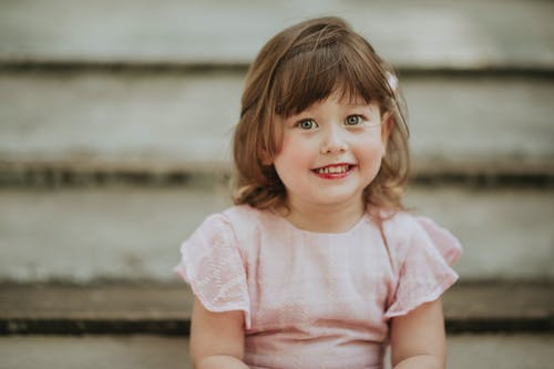 Charming little child with gray eyes and makeup looking at camera on staircase in daylight