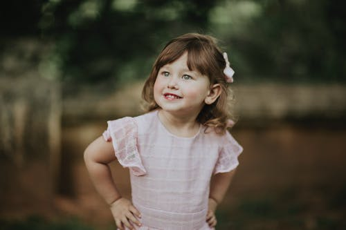 Pondering child in dress with hands on waist looking away in daytime on blurred background