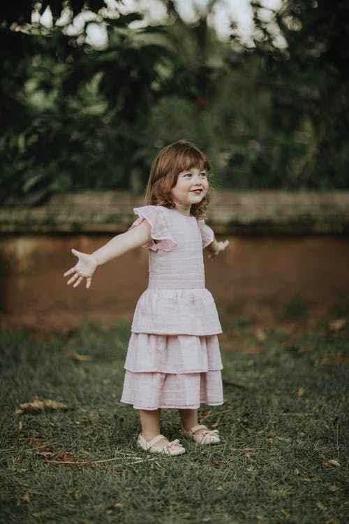 Cheerful child in dress and shoes looking away with arms apart on meadow in summer