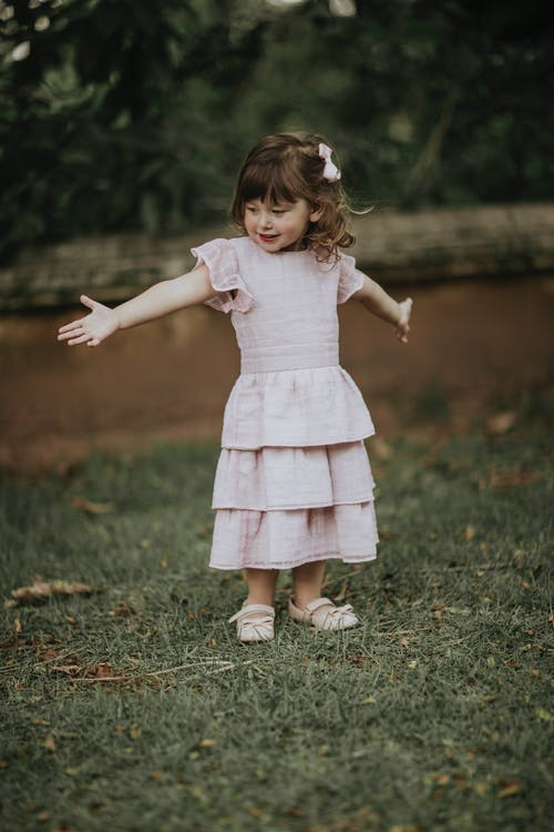 Charming child in dress and shoes looking away with outstretched arms on lawn in countryside