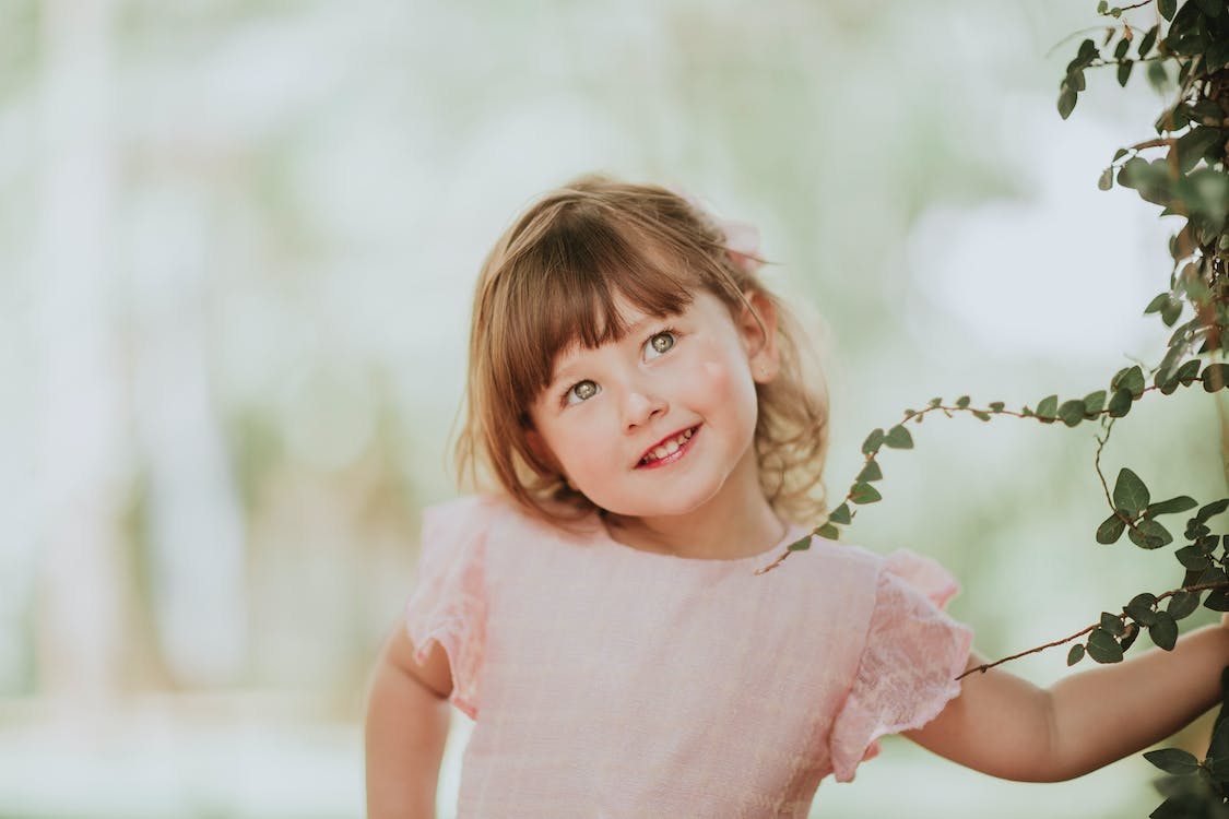 Contemplative child with brown hair and tilted head looking up against climbing plant on blurred background