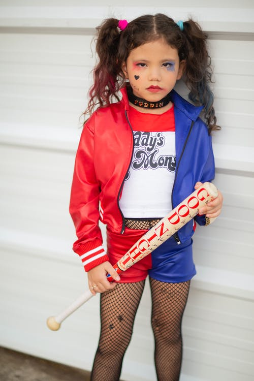 Adorable little girl with ponytails in stylish creative costume holding baseball bat while standing near white wall and looking at camera