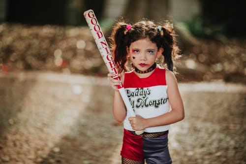 Little kid in costume with baseball bat