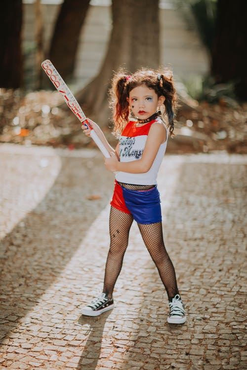 Full body of confident girl with makeup in trendy Halloween outfit standing on street while holding baseball bat and looking at camera
