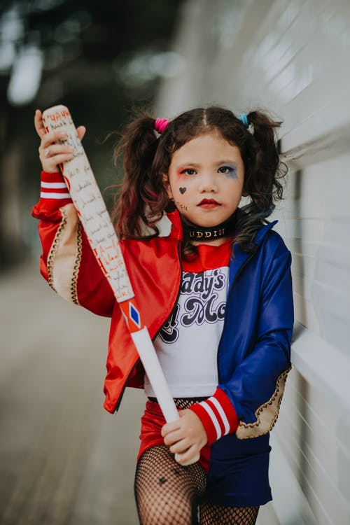 Calm kid in colorful outfit with baseball bat