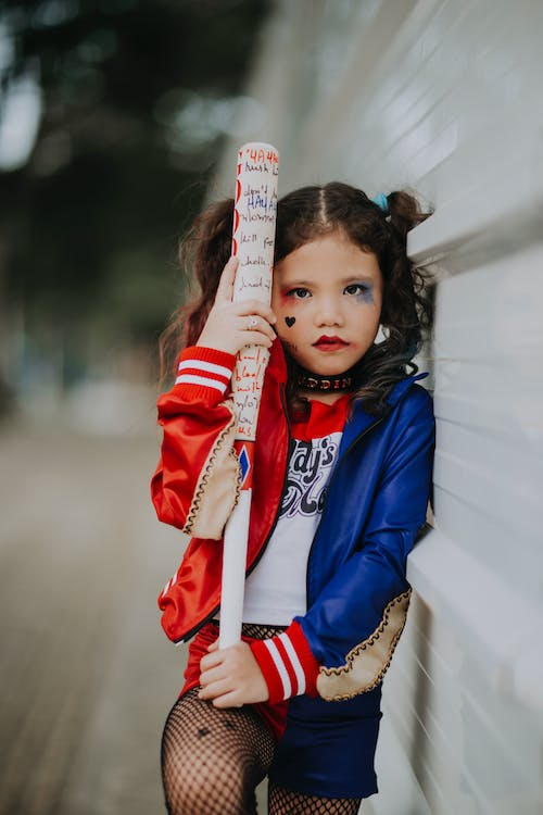Cute girl with ponytails and painted face in Halloween costume holding baseball bat while leaning on wall on street and looking at camera