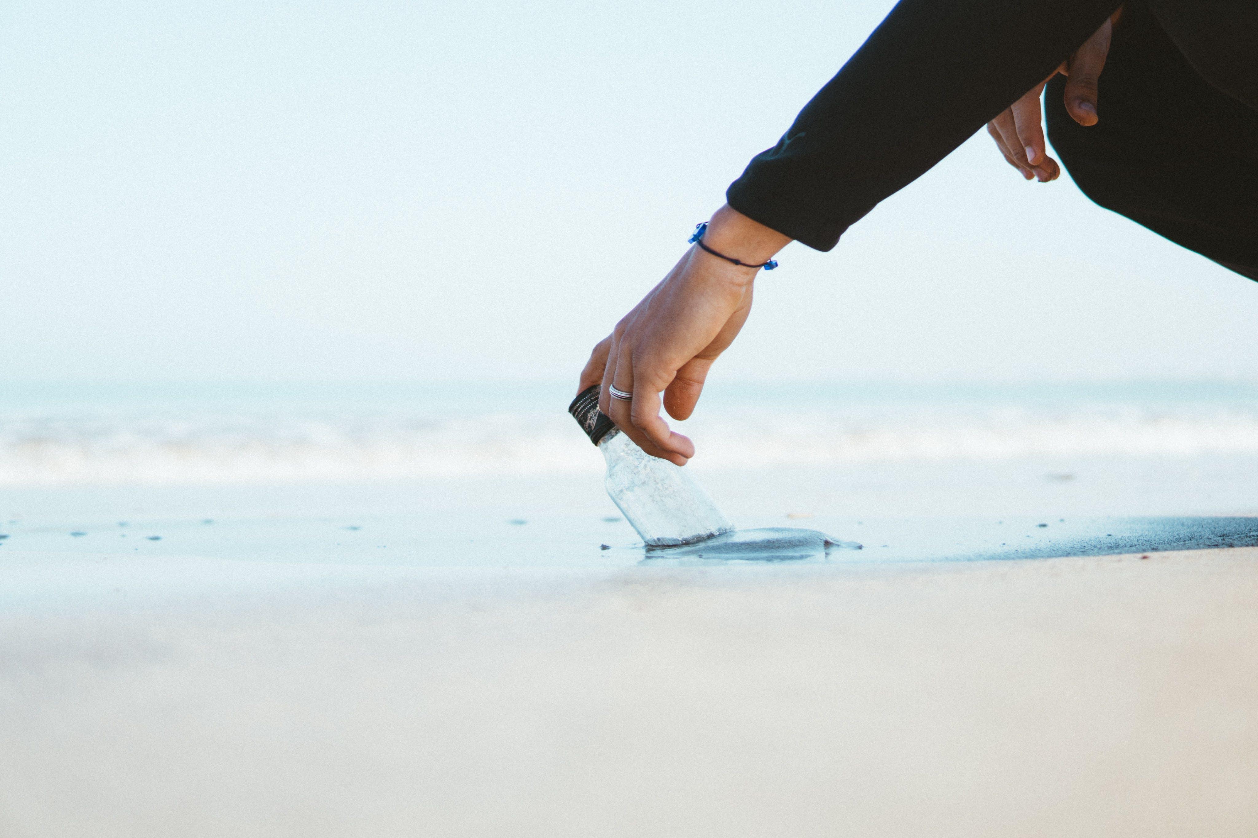 Person Wearing Black Long-sleeved Top Holding Bottle in Ocean