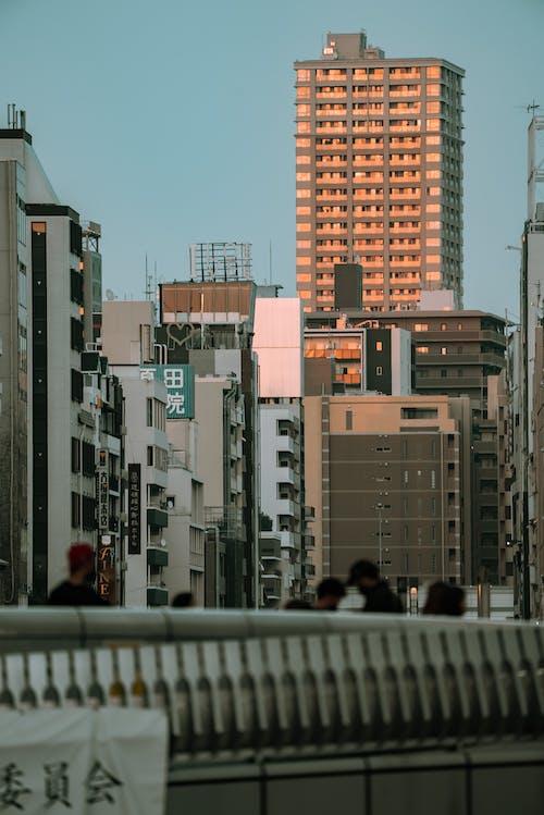People Walking on Street Near High Rise Buildings