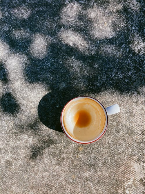 Cup of drunk cappuccino placed on table in sunny morning