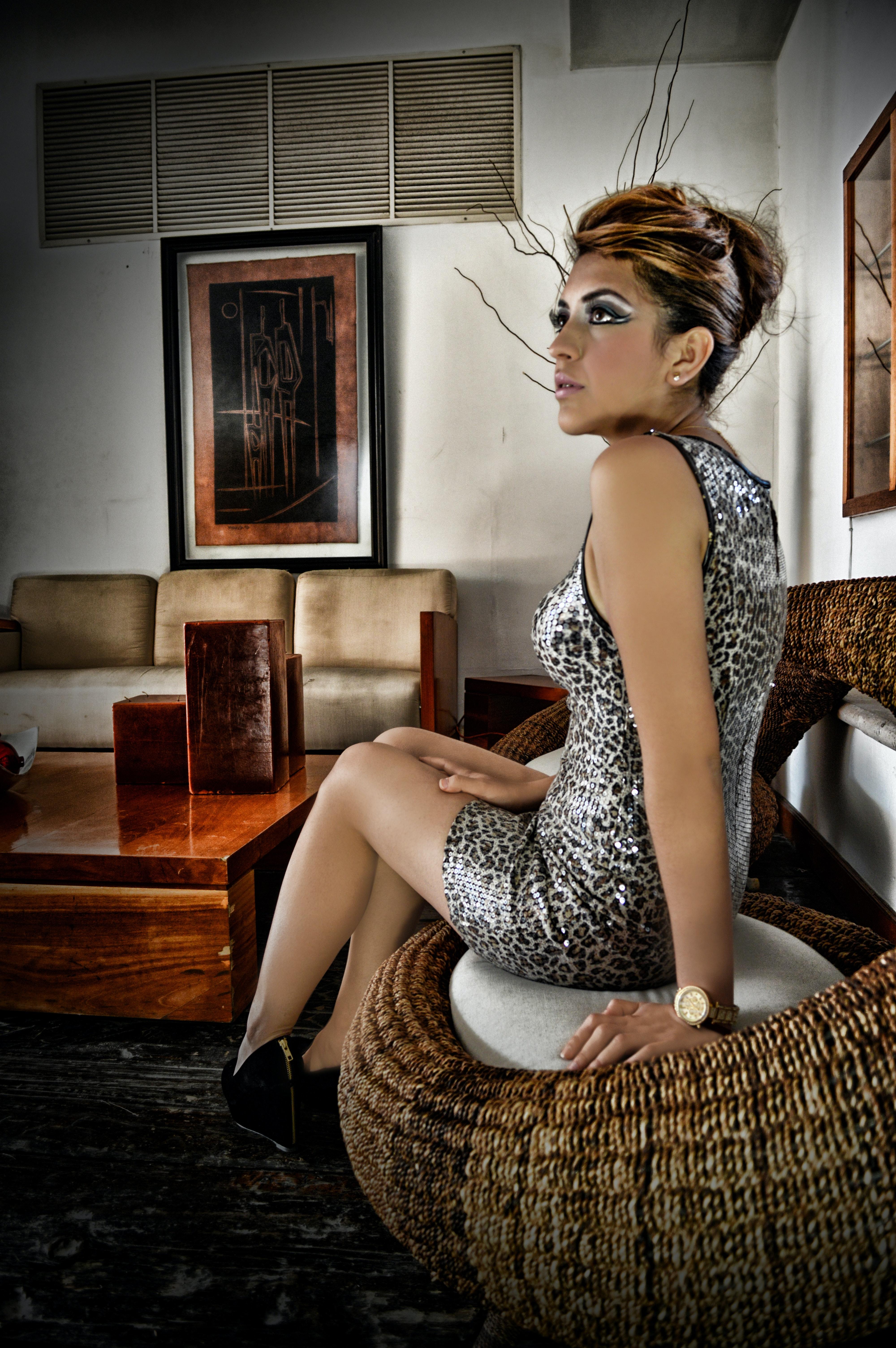 47d5c78c2ef5 Woman Wearing Leopard Print Sleeveless Mini Dress Sitting on Wicker ...