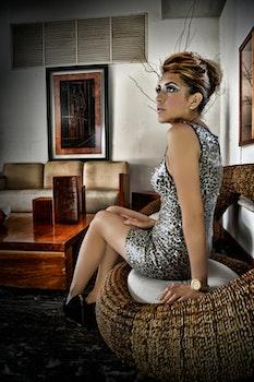 Woman Wearing Leopard Print Sleeveless Mini Dress Sitting on Wicker Brown Chair