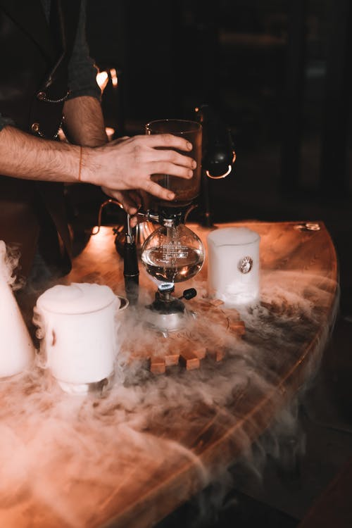 Anonymous guy brewing coffee with siphon