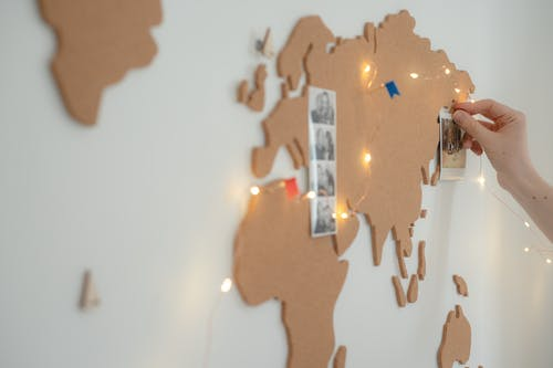 A Person Pinning Photos on the Map