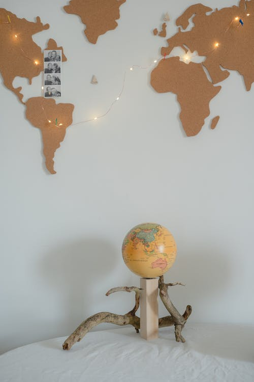 A Globe on the Table Near the Wall with Map and Fairy Lights