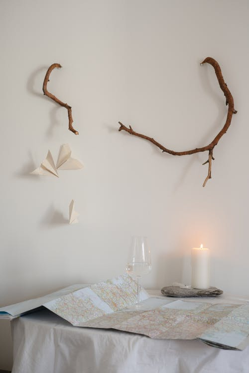 Brown Wooden Tree Branch on White Wall Near a Table with Wine Glass