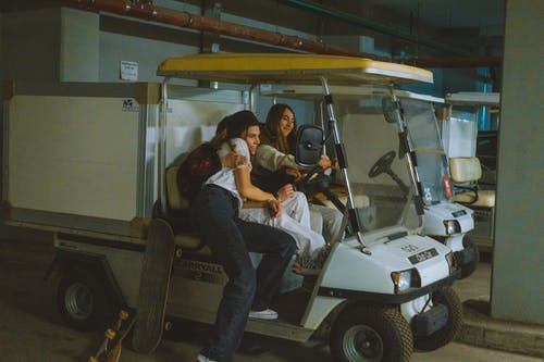 Man and Woman Riding White Golf Cart