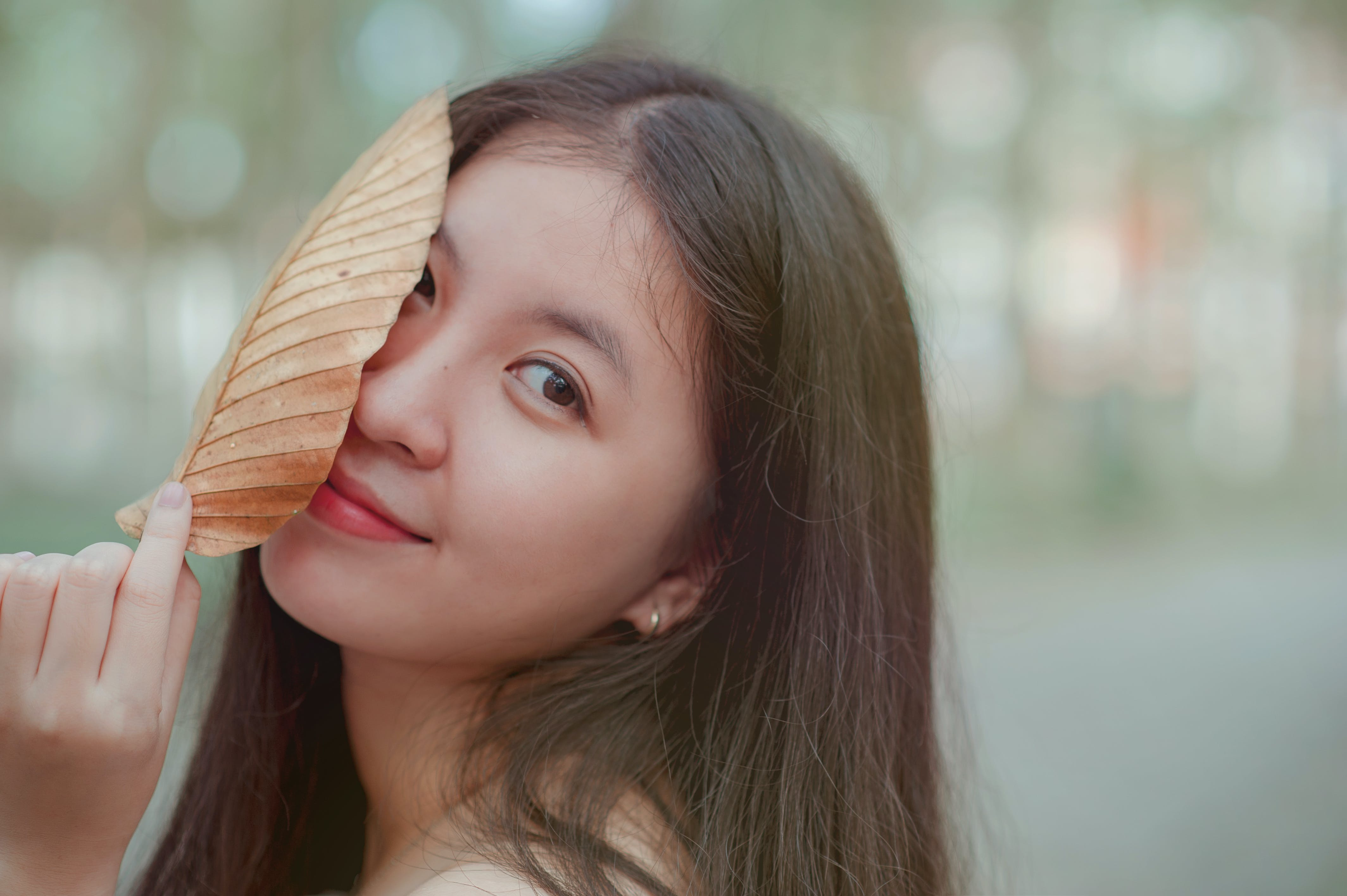 Photo of a Woman Holding a Dry Leaf