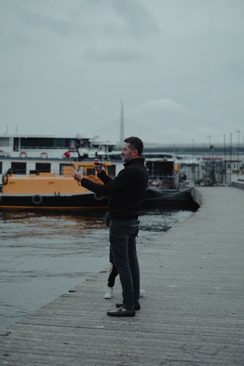 Unrecognizable man with child in casual clothes standing on wooden pier with boats on rippling river in city street in daylight under cloudy gray sky