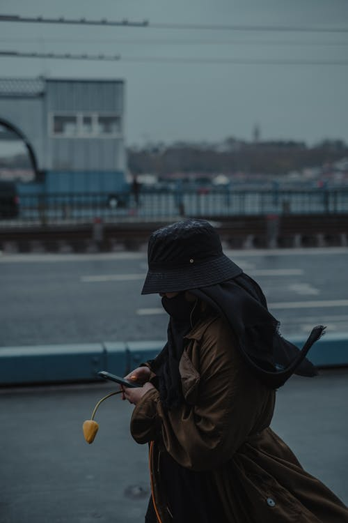 Side view of faceless female in warm coat and hat with mask and flower walking in town district while texting on cellphone near road in daylight