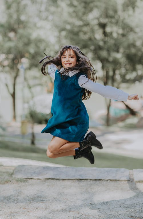Full body of cheerful ethnic girl in stylish dress and boots smiling while jumping in park on sunny day
