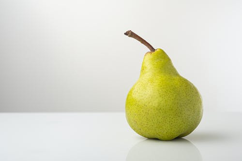 Close-Up Photo of a Pear on a White Surface