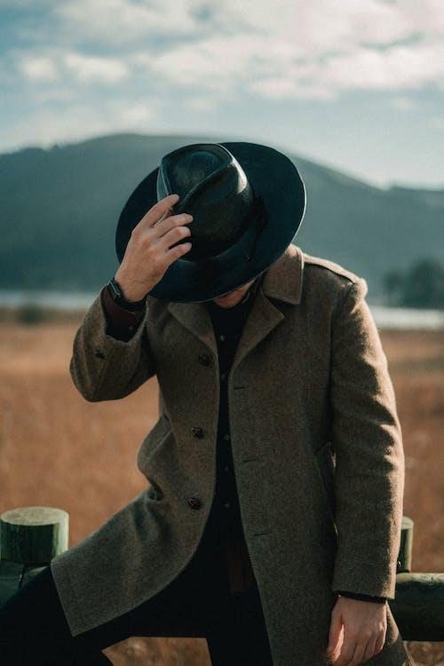 Man in Brown Coat Holding Black Hat