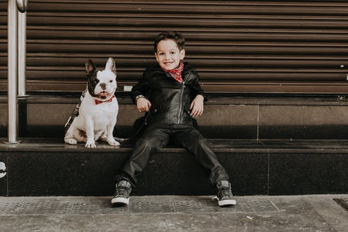 Full length of smiling boy in stylish clothes sitting with obedient French bulldog on black stairway on street and looking at camera in daytime