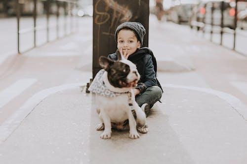 Boy with French bulldog sitting on sidewalk on street