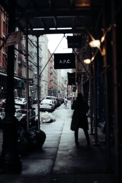 Man in Black Coat Walking on Sidewalk during Night Time